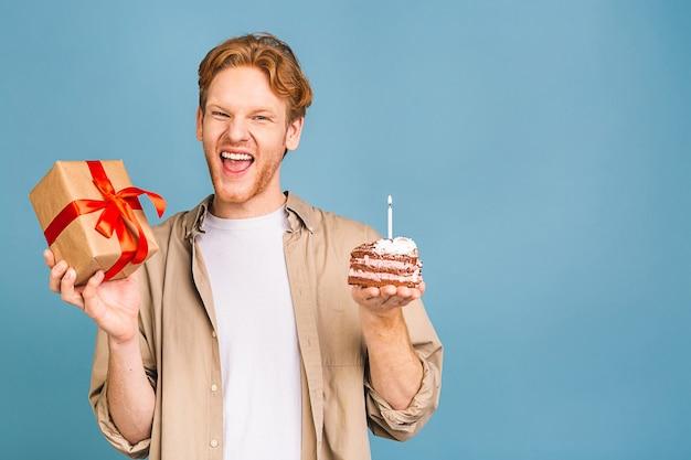 Porträt eines fröhlichen jungen glücklichen mannes, der einen geburtstagskuchen mit kerze und einer geschenkbox hält