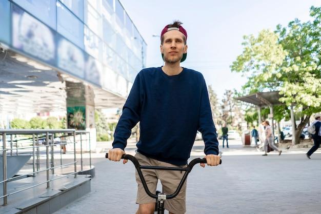Porträt eines fröhlichen jungen mannes auf dem fahrrad, der in den straßen der stadt fährt