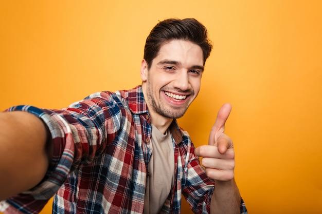 Porträt eines fröhlichen jungen mannes, der ein selfie macht