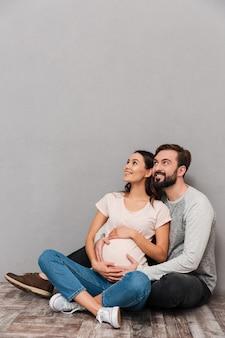 Porträt eines fröhlichen jungen mannes, der seine schwangere frau umarmt