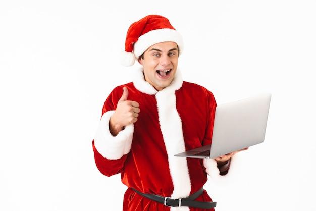 Porträt eines fröhlichen jungen mannes gekleidet im weihnachtsmannkostüm, das isoliert über weißem raum steht und laptop-computer hält