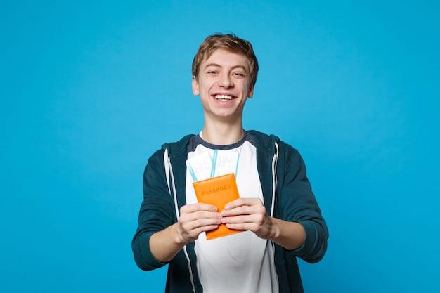 Porträt eines fröhlichen jungen mannes in freizeitkleidung halten reisepass, bordkarte einzeln auf blauer wandwand. menschen aufrichtige emotionen, lifestyle-konzept.