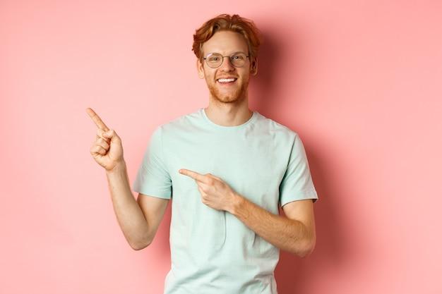 Porträt eines fröhlichen jungen mannes mit roten haaren, der eine brille trägt und mit den fingern auf die obere linke ecke zeigt.