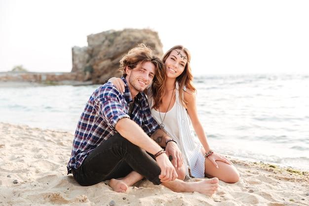 Porträt eines fröhlichen jungen paares, das am strand sitzt