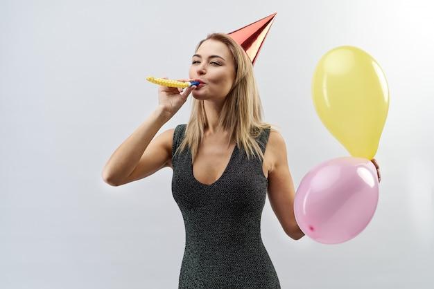 Porträt eines fröhlichen jungen stilvollen weiblichen mädchens, das für ein porträt auf lokalisiertem hintergrund mit zeremoniellen attributen aufwirft (in der haube für eine party, pfeife und luftballons pfeifen)
