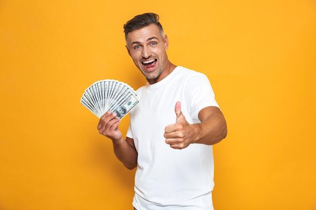 Porträt eines fröhlichen kerls der 30er jahre im weißen t-shirt, der lächelt und einen haufen geld isoliert auf gelb hält