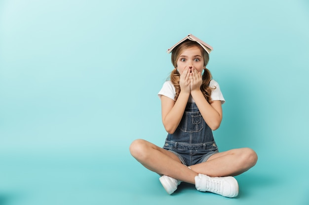 Porträt eines fröhlichen kleinen mädchens, das isoliert über blauer wand sitzt und ein buch auf dem kopf hält