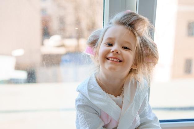 Porträt eines fröhlichen kleinen mädchens in lockenwicklern auf dem fenster