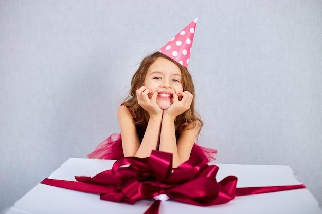 Porträt eines fröhlichen kleinen mädchens in rosa kleid und hut legte ihre ellbogen auf eine große geschenkbox, zu hause geburtstagsparty-streamer, alles gute zum geburtstag. feiern