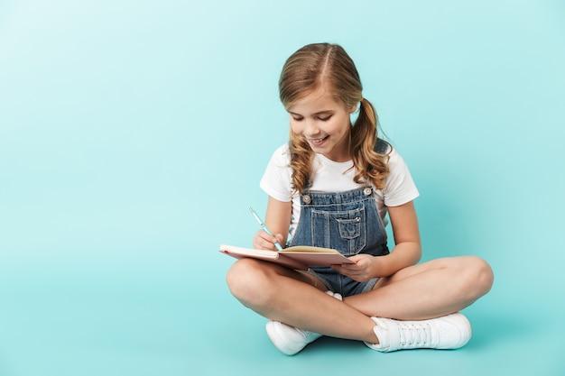 Porträt eines fröhlichen kleinen mädchens isoliert über blauer wand, in ein notizbuch schreibend