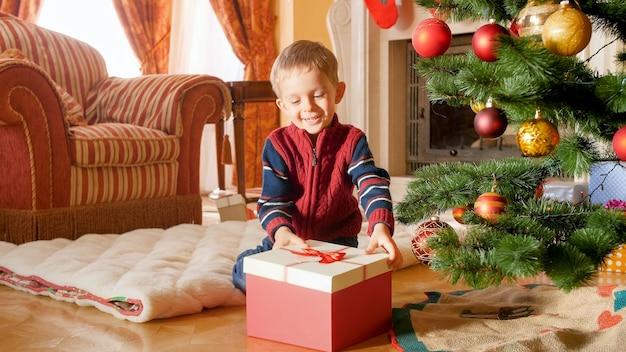 Porträt eines fröhlichen lachenden kleinkindjungen, der eine weihnachtsgeschenkbox öffnet, während er auf dem boden unter dem weihnachtsbaum sitzt