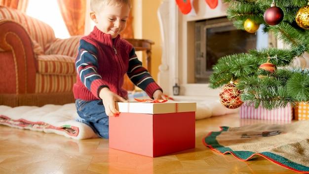 Porträt eines fröhlichen lächelnden kleinen jungen, der eine große kiste mit weihnachtsgeschenk betrachtet