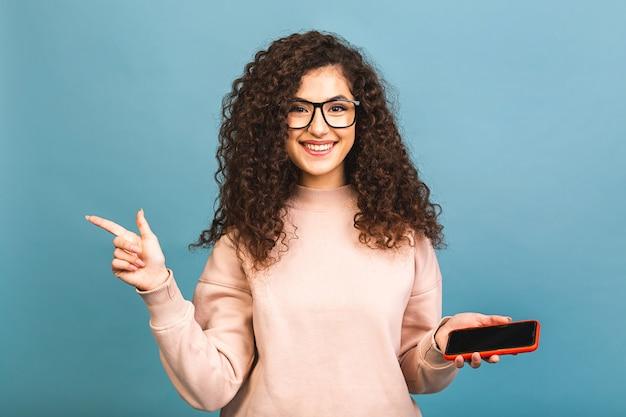 Porträt eines fröhlichen lässigen lockigen mädchens, das ein mobiltelefon hält und ihren finger weg von lokalisiert auf blauem hintergrund zeigt.