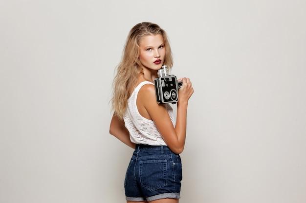 Porträt eines fröhlichen mädchens, das in weißer modekleidung posiert, eine retro-kamera in der hand hält und wegschaut.