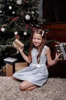 Porträt eines fröhlichen mädchens gekleidet im kleid, das weihnachtsgeschenkboxen hält