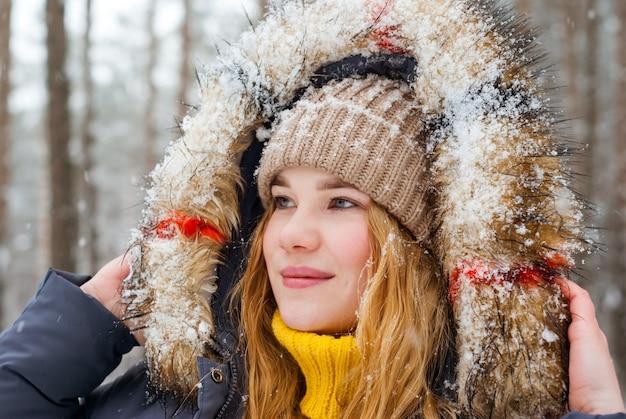 Porträt eines fröhlichen mädchens in einer schneebedeckten pelzhaube im winterpark
