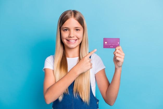 Porträt eines fröhlichen mädchens mit blonden haaren, das auf eine bankkarte zeigt, trägt ein weißes t-shirt, das auf pastellblauem hintergrund isoliert ist