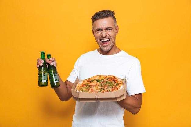 Porträt eines fröhlichen mannes der 30er jahre in weißem t-shirt, der bier trinkt und pizza isst, während er isoliert auf gelb steht