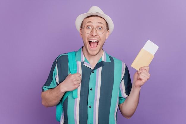 Porträt eines fröhlichen, positiv zufriedenen kerls, der flugtickets hält, schreien mit offenem mund auf violettem hintergrund