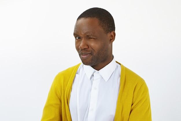Porträt eines fröhlichen positiven jungen dunkelhäutigen mannes, der blinkt und spielerisch in die kamera lächelt, als ob er mit der schönen frau flirtet. menschliche mimik, emotionen, gefühle und reaktionen
