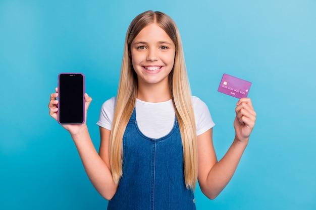 Porträt eines fröhlichen, schönen blonden mädchens mit langen haaren, das telefon zeigt, kaufen sie online ein lässiges outfit, das auf pastellblauem hintergrund isoliert ist