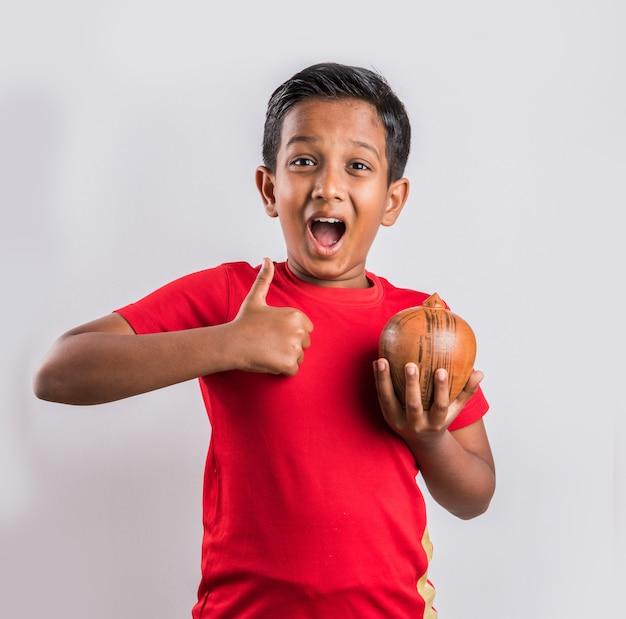 Porträt eines fröhlichen süßen kleinen indischen asiatischen kindes, das sparschwein mit büchern hält und die kamera isoliert auf weißem hintergrund betrachtet
