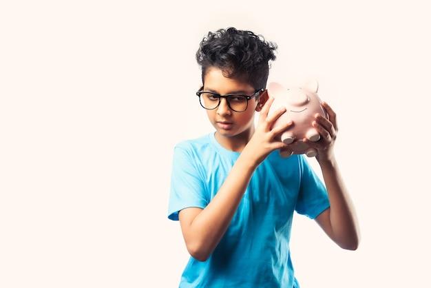 Porträt eines fröhlichen süßen kleinen indischen asiatischen kindes, das sparschwein mit büchern isoliert über weißer wand hält