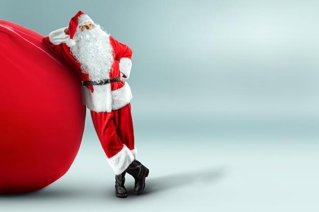 Porträt eines fröhlichen weihnachtsmannes in einem roten anzug, der eine große tasche trägt