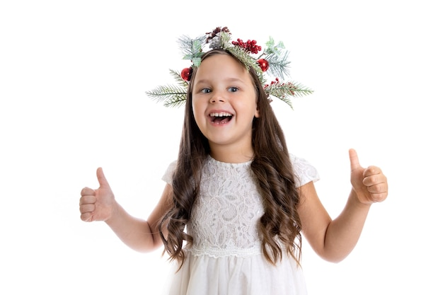 Porträt eines fröhlichen, zufriedenen kaukasischen mädchens im weißen kleid mit weihnachtskranz und daumen hoch...