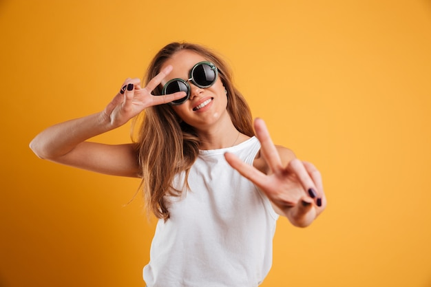 Porträt eines frohen jungen mädchens in der sonnenbrille, die frieden zeigt