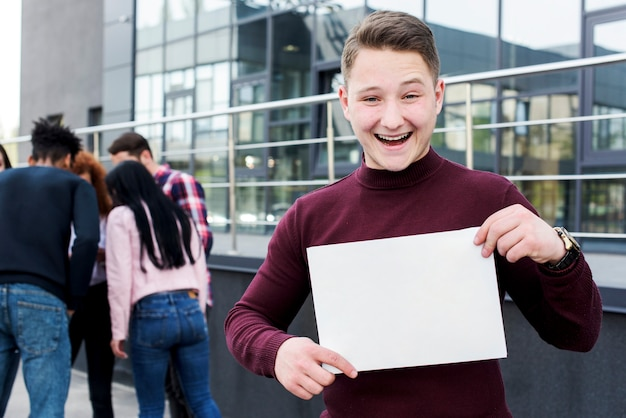 Porträt eines frohen jungen mannes, der das leere plakat steht nahes gebäude hält