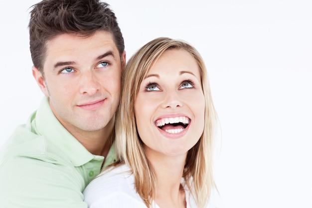 Porträt eines frohen paares, welches die spitzenstellung gegen einen weißen hintergrund betrachtet