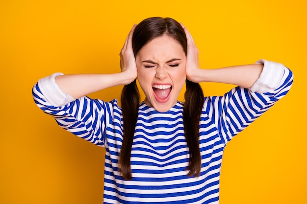 Porträt eines frustrierten mädchens schließen die hände, das ohr ignoriert laute geräusche, missverständnisse, schreie, schreien, tragen gut aussehende kleidung, die über glänzendem hintergrund isoliert ist