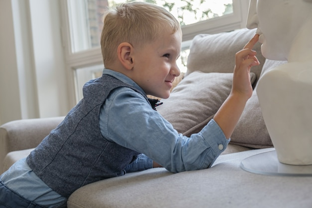 Porträt eines fünfjährigen jungen im profil junge berührt eine gipsbüste, während er auf der couch liegt