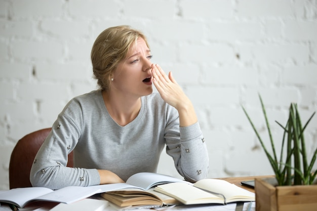 Porträt eines gähnenden studentenmädchens am schreibtisch