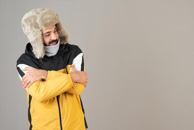 Porträt eines gefrorenen bärtigen mannes in warmer kleidung, der steht und posiert.
