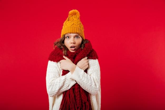 Porträt eines gefrorenen mädchens kleidete im winterhut an