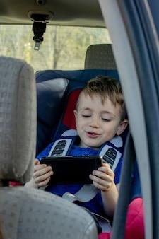 Porträt eines gelangweilten kleinen jungen, der in einem autositz sitzt. sicherheit des transports von kindern.