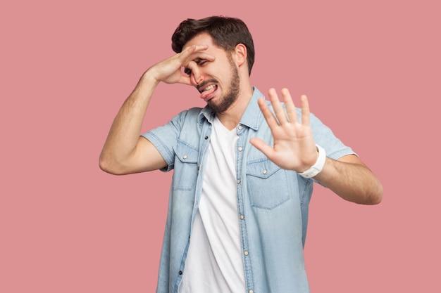 Porträt eines gelangweilten oder verwirrten, gutaussehenden, bärtigen jungen mannes im blauen hemd im casual-stil, der seine nase kneift und das handzeichen mit der stoppgeste zeigt. indoor-studioaufnahme, isoliert auf rosa hintergrund.