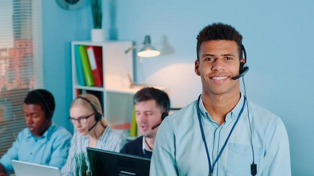 Porträt eines gemischtrassigen kundendienstmitarbeiters im headset, der den kameraarbeitskollegen anlächelt...