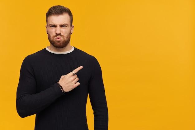 Porträt eines genervten, zusammengekniffenen mannes mit brünetten haaren und bart. trage einen schwarzen pullover. und zeigefinger nach rechts auf den kopierbereich, isoliert über der gelben wand