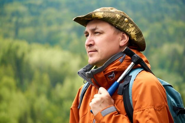 Porträt eines geologen mit rucksack und geologischem hammer gegen die berglandschaft