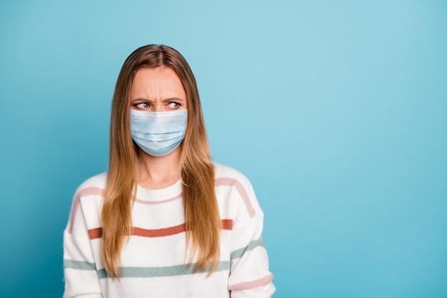 Porträt eines gereizten kranken mädchens, das eine sicherheitsmaske mit grippesymptom trägt, isoliert auf blauem hintergrund
