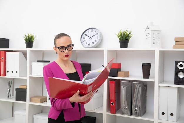 Porträt eines geschäftsartmädchens, das dokumente in einem roten ordner sucht