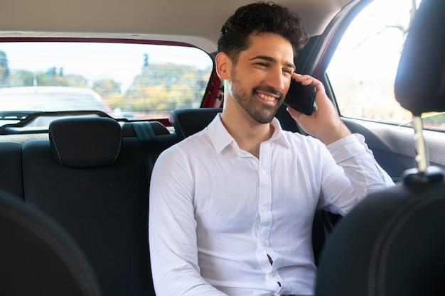 Porträt eines geschäftsmannes, der auf dem weg zur arbeit in einem auto telefoniert?