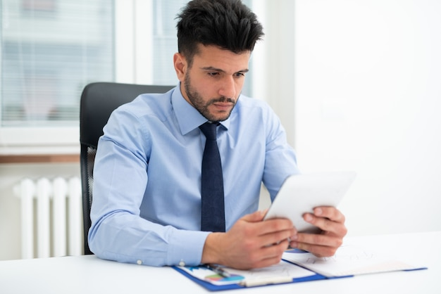Porträt eines geschäftsmannes, der ein tablett in seinem büro benutzt