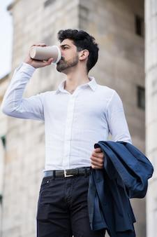 Porträt eines geschäftsmannes, der eine tasse kaffee auf dem weg zur arbeit im freien trinkt. unternehmenskonzept.