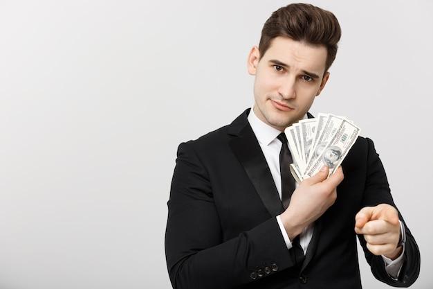 Porträt eines geschäftsmannes, der geld zeigt und mit den fingern auf weißem hintergrund zeigt