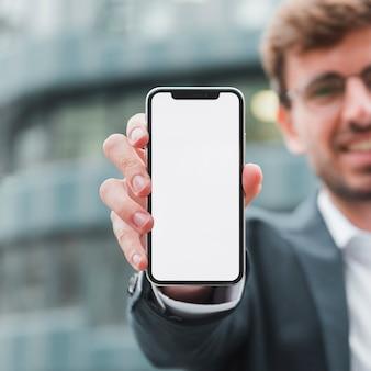 Porträt eines geschäftsmannes, der handy des weißen schirmes in richtung zur kamera zeigt