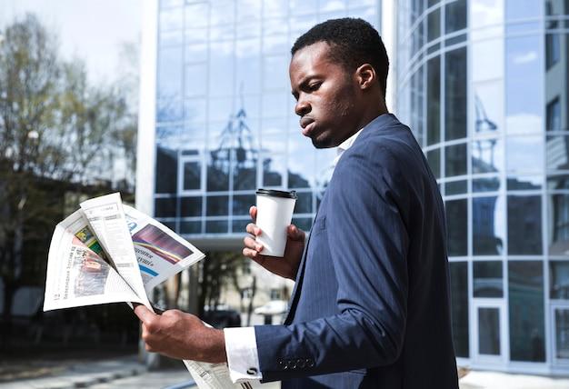 Porträt eines geschäftsmannes, der vor dem gebäude hält den wegwerfkaffee liest die zeitung steht